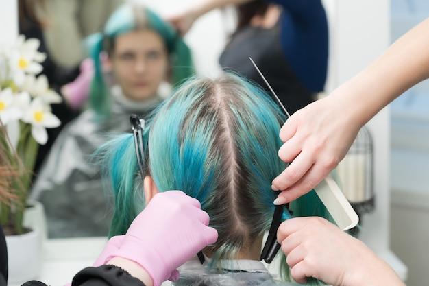 Achteraanzicht van vrouwelijk hoofd met smaragdgroene haarkleur en regrown haarwortels. vrouw zit in stoel bij spiegel, twee kappers kammen het haar van de klant