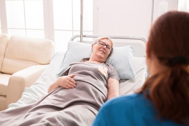 Achteraanzicht van vrouwelijke arts in verpleeghuis praten met oude vrouw in bed liggen.