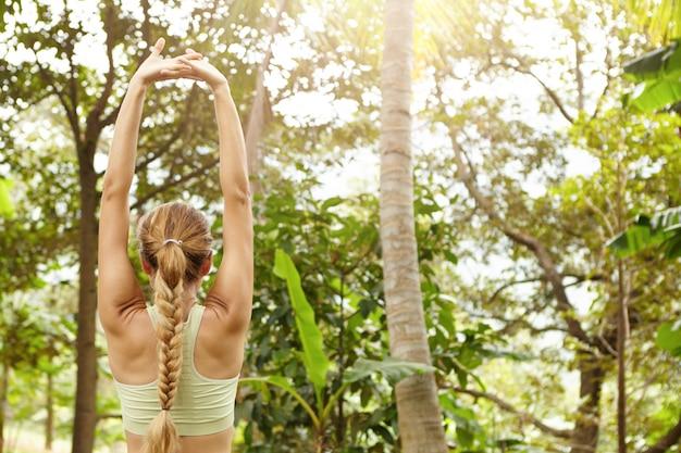 Achteraanzicht van vrouwelijke atleet met mooi atletisch lichaam en vlecht spieren uitrekken, haar armen opheffen tijdens het opwarmen in park voor ochtend trainingssessie.