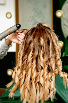 Achteraanzicht van vrouwelijke kappers handen womens haar curling met krultang in een kapsalon