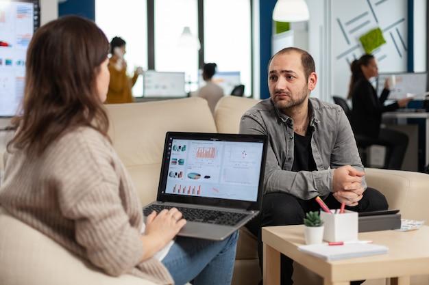 Achteraanzicht van vrouwelijke ondernemer zittend op de bank met behulp van laptop