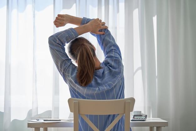 Achteraanzicht van vrouwelijke strekkende rugpijn als gevolg van werken op afstand negatieve aspecten van thuiswerken