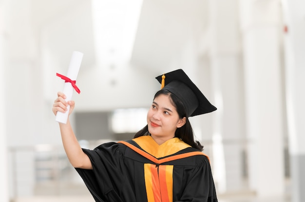 Achteraanzicht van vrouwelijke universitair afgestudeerden met diploma houden