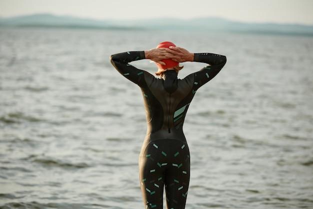 Achteraanzicht van vrouwelijke zwemmer in zwembroek die wegkijkt naar de zonsondergang terwijl hij in het meer staat