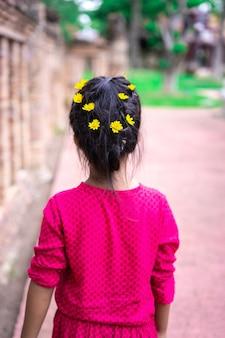 Achteraanzicht van weinig aziatisch meisje in een rode jurk met mooi haar en gele bloem wandelen in het park