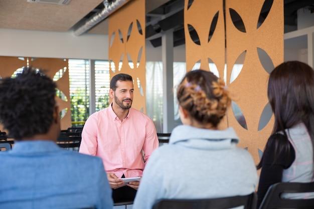Achteraanzicht van werknemers luisteren naar jonge consultant