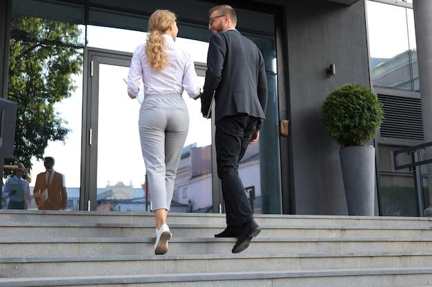 Achteraanzicht van zakenman en vrouw die in het kantoorcentrum lopen.