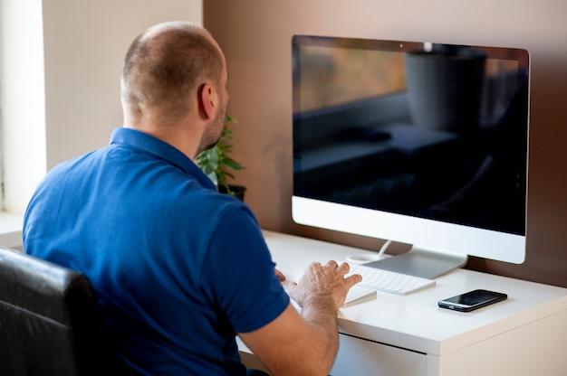 Achteraanzicht van zakenman met behulp van computer zittend aan een bureau in kantoor aan huis