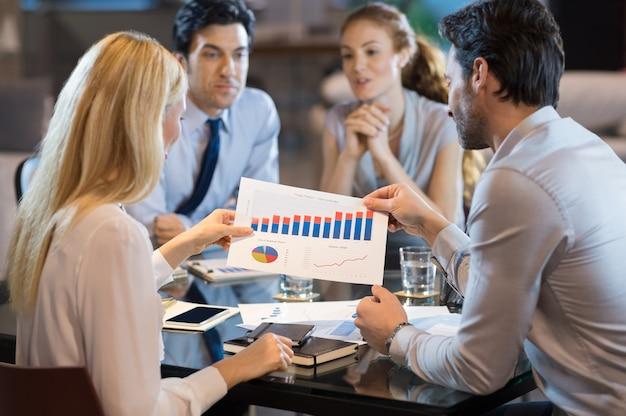 Achteraanzicht van zakenmensen analyseren jaarverslag met voortgangsgrafieken.