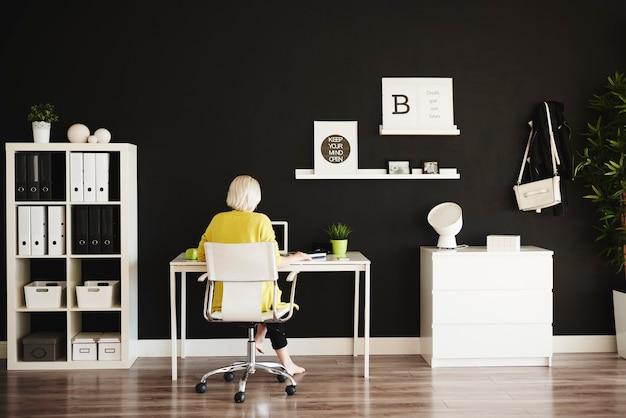 Achteraanzicht van zakenvrouw die op kantoor aan huis werkt
