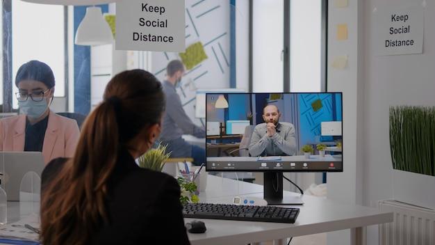 Achteraanzicht van zakenvrouw met gezichtsmasker discussiëren op videocall-conferentie met externe collega's. uitvoerende freelancer aan het werk in een nieuw normaal bedrijfskantoor tijdens een pandemie van het coronavirus