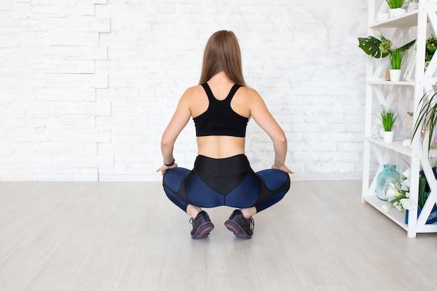 Achteraanzicht van zittende sportieve vrouw die beenkappen draagt. achteraanzicht van sportieve vrouw
