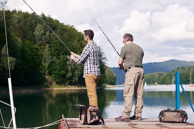 Achteraanzicht van zoon en vader vissen