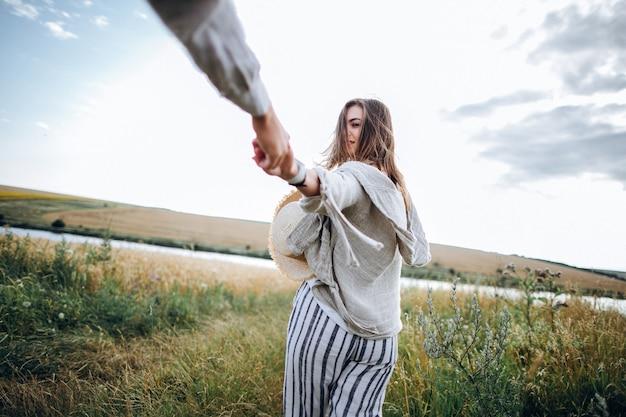 Achteraanzicht volg mij. gelukkige paar verliefd knuffelen, zoenen en lachend tegen de hemel in het veld.
