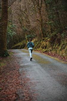Achteraanzicht volledige lengte fit vrouwelijke jogger in sportkleding draait op onverharde weg in dikke herfst bos