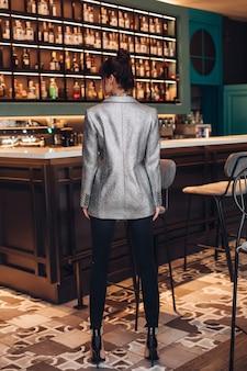 Achteraanzicht volledige lengte van mannequin in sprankelende zilveren jas, zwarte broek en hoge hakken met kapsel in trendy bar.
