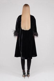Achteraanzicht volledige lengte vrouwelijke mannequin permanent in zwarte kleding met perfect gezond haar geïsoleerd op witte studio achtergrond. achteraanzicht vogue vrouw in trendy kleding poseren binnen