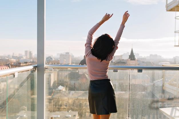 Achteraanzicht vrolijke jonge aantrekkelijke vrouw die zich uitstrekt op terras in zonnige ochtend op grote stad. vrouw, groot succes, geluk, ontspannen, opgewekte stemming,