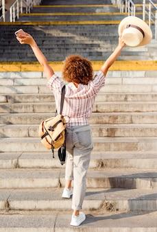 Achteraanzicht vrouw de trap buitenshuis lopen