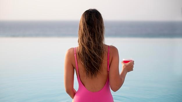 Achteraanzicht vrouw die in het zwembad staat