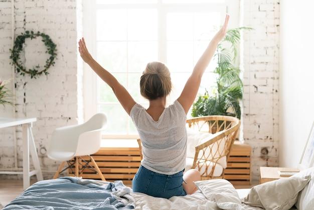 Achteraanzicht vrouw die zich uitstrekt in slaapkamer