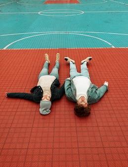 Achteraanzicht vrouw en man liggend op een basketbalveld