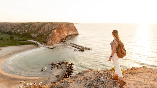 Achteraanzicht vrouw genieten van de zonsondergang aan een kust met kopie ruimte