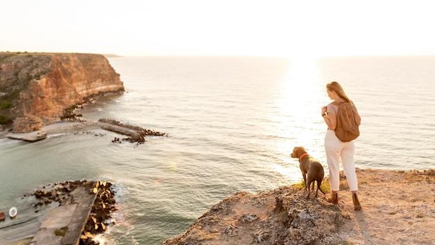 Achteraanzicht vrouw genieten van de zonsondergang met haar hond met kopie ruimte
