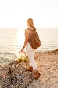 Achteraanzicht vrouw genieten van de zonsondergang