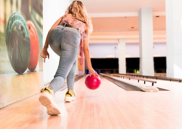 Achteraanzicht vrouw gooien bowlingbal