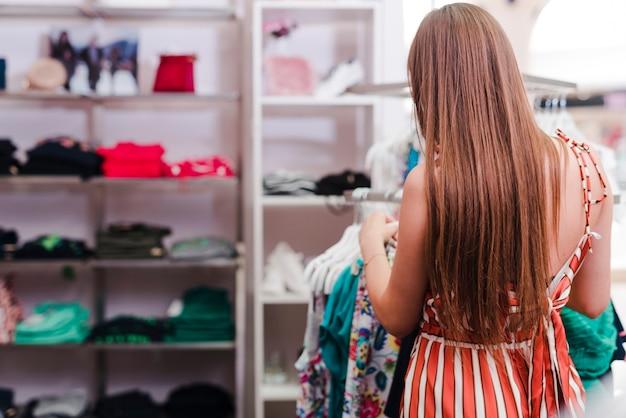 Achteraanzicht vrouw kijken naar kleding