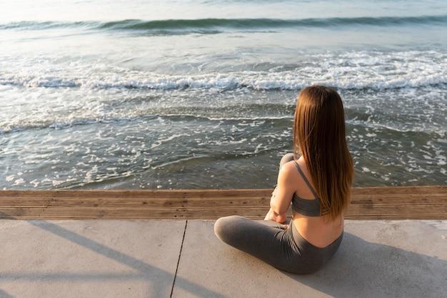 Achteraanzicht vrouw kijkt naar de zee met kopie ruimte