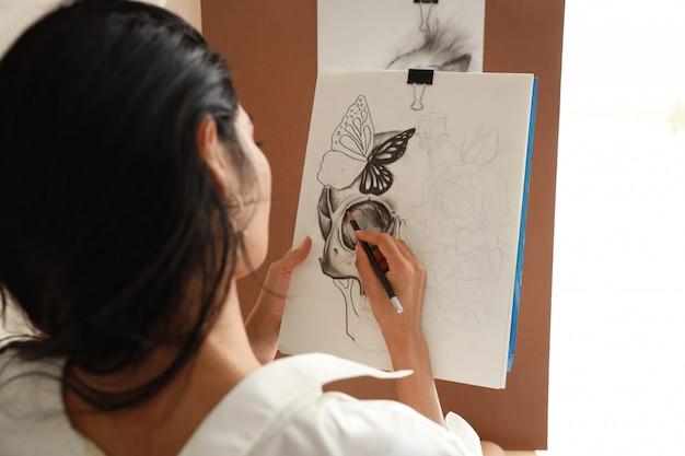 Achteraanzicht vrouw kunstenaar in wit overhemd tekening foto met potlood (vrouw levensstijl concept)