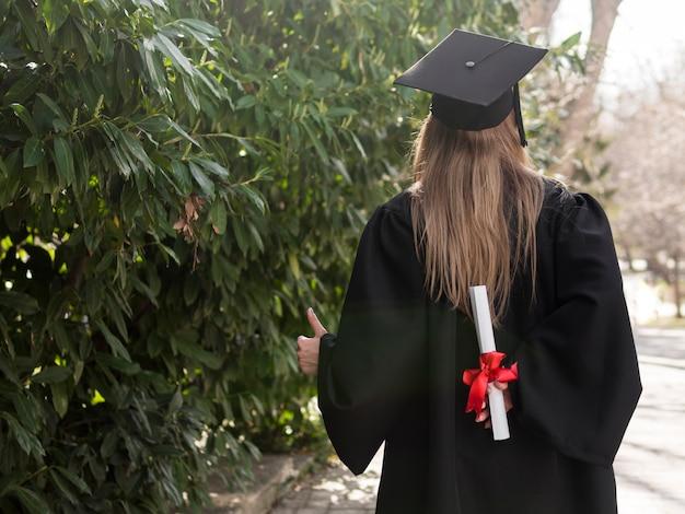 Achteraanzicht vrouw met haar diploma