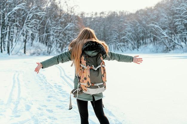 Achteraanzicht vrouw met rugzak op winterdag