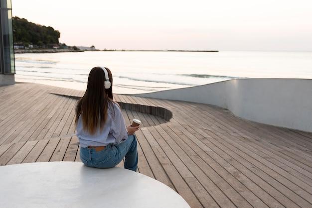 Achteraanzicht vrouw ontspannen terwijl het dragen van een koptelefoon