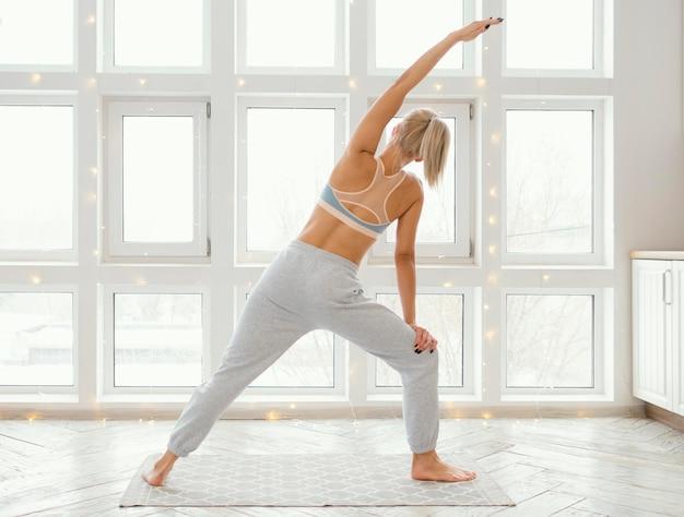 Achteraanzicht vrouw op mat oefenen