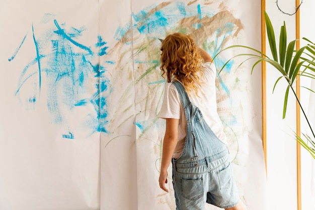 Achteraanzicht vrouw schilderij aan de muur