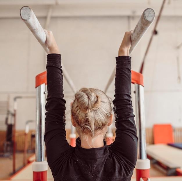 Achteraanzicht vrouw training voor gymnastiek kampioenschap