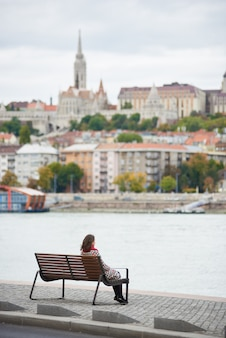 Achteraanzicht vrouw zit op een bankje aan de kade van boedapest in de buurt van de rivier