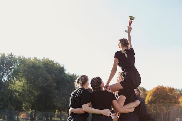 Achteraanzicht vrouwelijk team dat een trofee wint