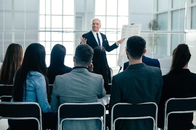 Achteraanzicht. werknemers van het bedrijf applaudisseren tijdens een werkvergadering. succes concept