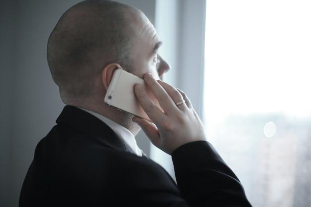 Achteraanzicht .zakenman met smartphone kijkt uit het raam van de office.photo met kopieerruimte
