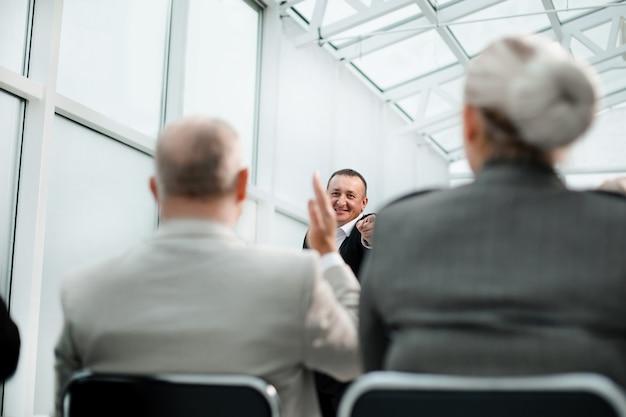 Achteraanzicht zakenmensen stellen vragen tijdens een zakelijk seminar