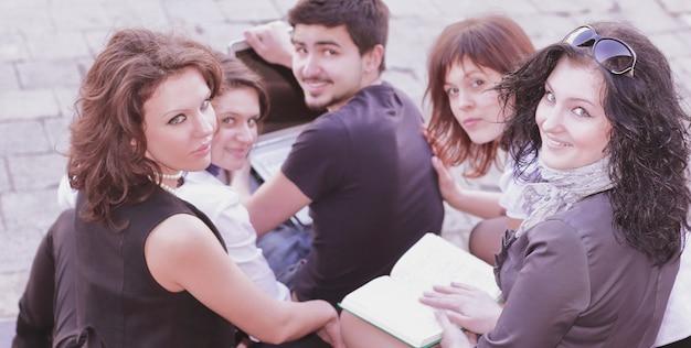 Achteraanzichtgroep studenten die zich voorbereiden op colleges met behulp van laptop