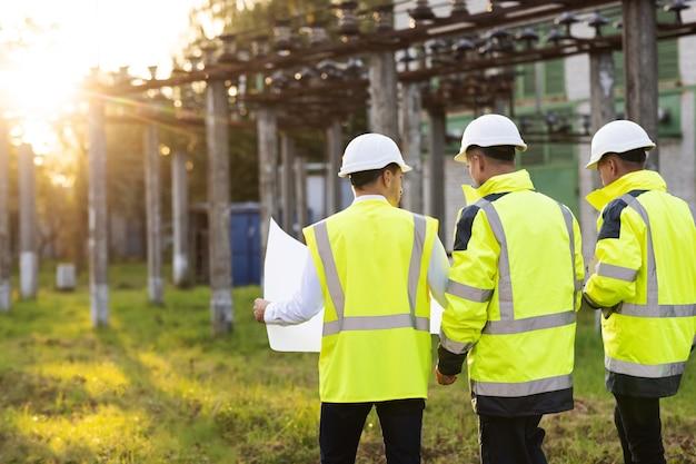 Achteraanzichtgroep van diverse specialisten in het midden van de bouwplaats die ze het plan analyseren