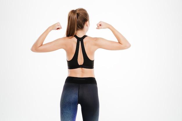 Achteraanzichtportret van een geschiktheidsvrouw die haar geïsoleerde biceps toont