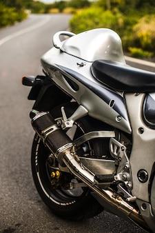 Achterbank en wiel van een zilverkleurige motorfiets.