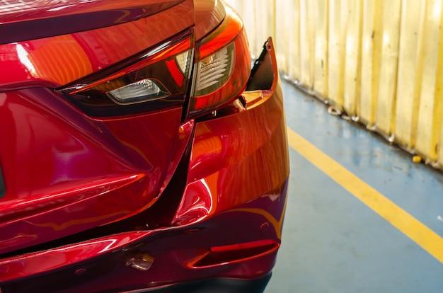 Achterbumper gedeukte rode auto