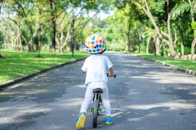Achtereind van schattige aziatische 2 jaar peuter jongen kind dragen veiligheidshelm leren